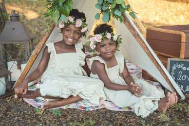 Two young Dallas girls sitting under a tent