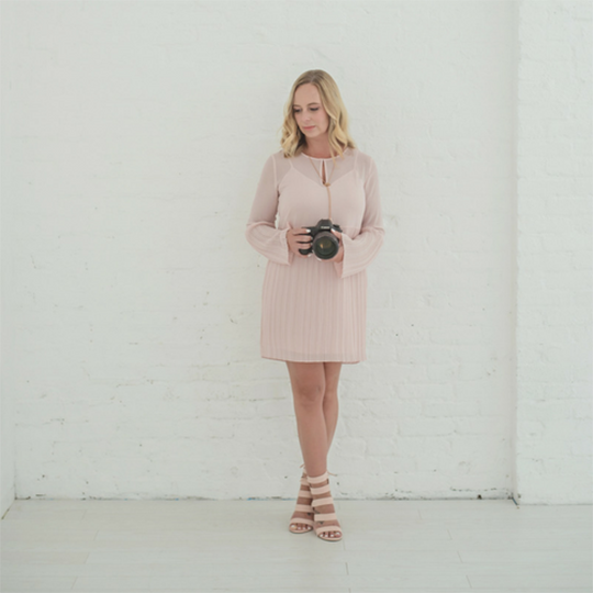 Alyssa Turner in a pink dress holding a camera